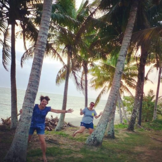 Mother and daughter having fun at sunset among the palm trees in Fiji