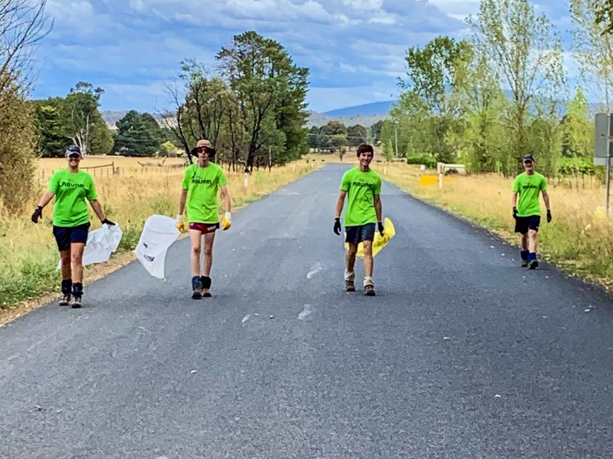 Green shirted trekkers picking up rubbish